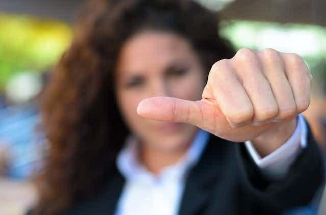 Una mujer muestra su mano con el pulgar en posición horizontal.