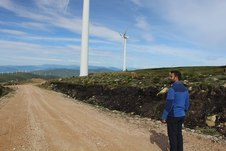The author stood on a road next to a bank of excavated peat and two wind turbines.