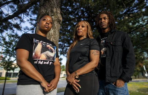 Three Black people, a young woman, her mother and brother, stand in front of a tree.