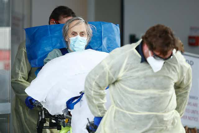 A lady, wearing a face mask, in a stretcher being wheeled by two paramedics