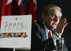 A man gestures while speaking with a report entitled Shape the Future in the foreground.