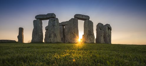Central stones of Stonehenge at sunset.