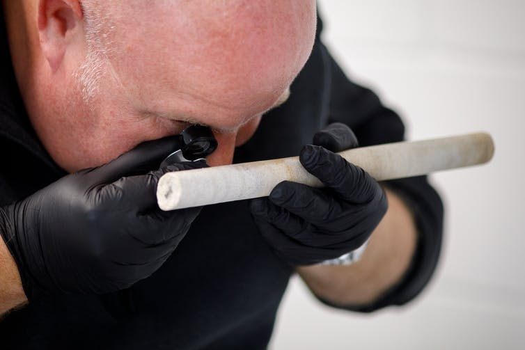Man examining stone rod.