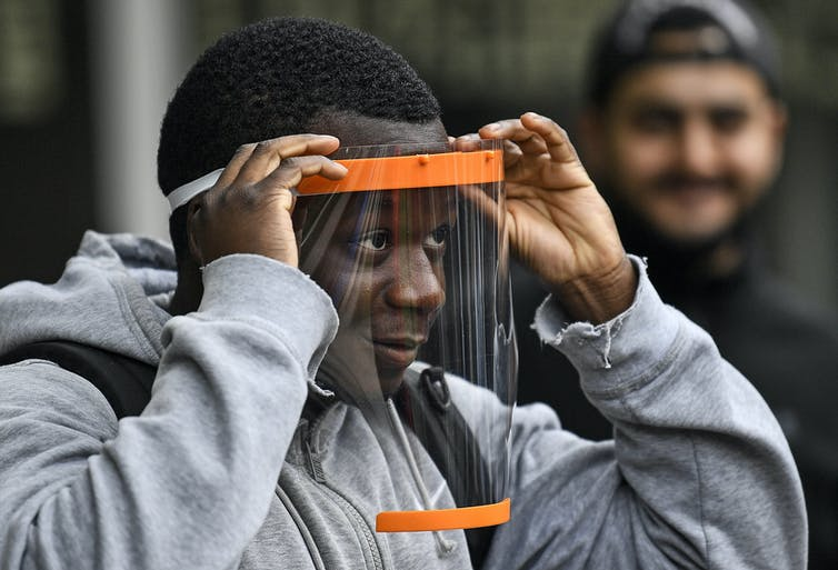 A teenager tries on a face shield with a full face visor as a classmate stands behind him smiling.