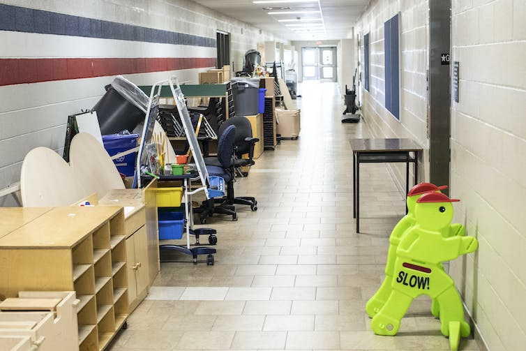 Desks, chairs and shelving units are pushed against the wall of an empty corridor in a school.