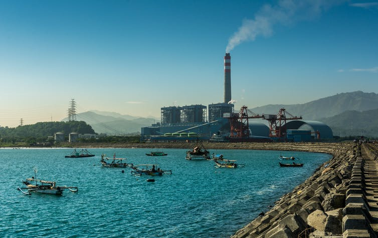 A coastal coal fired power station in Indonesia surrounded by small boats in the bay.