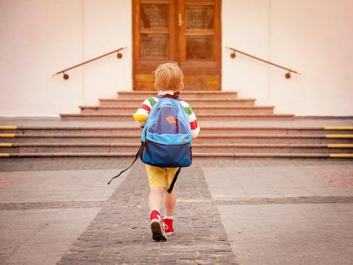 Niño de espaldas con mochila a la puerta de un colegio.