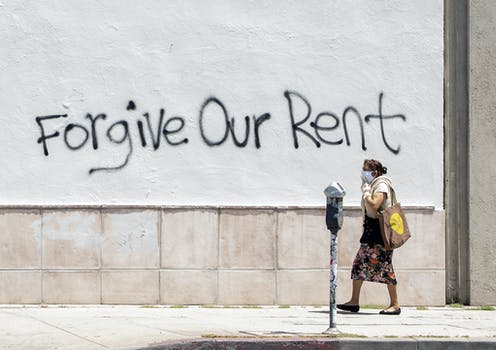 """A woman wearing a mask walks past a wall bearing graffiti that reads """"forgive our rent"""" on La Brea Ave in Los Angeles, California."""