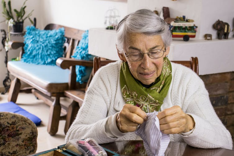 An older woman wearing a green scarf with a fabric face mask in her hands and sewing supplies on the table beside her.