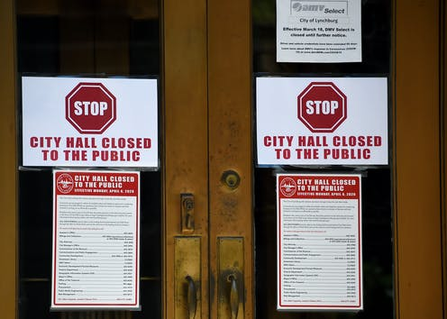 Signs on the main entrance to the the Lynchburg, Virginia, City Hall say it's closed during the outbreak of COVID-19.coronavirus, on May 5, 2020.