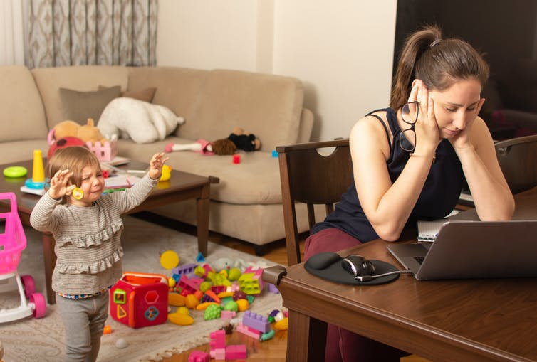 A white woman sits at a table in front of a laptop with her head in her hands as a toddler tries to get her attention.