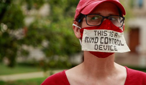 """Woman wearing mask with the message """"This is a mind contol device'."""