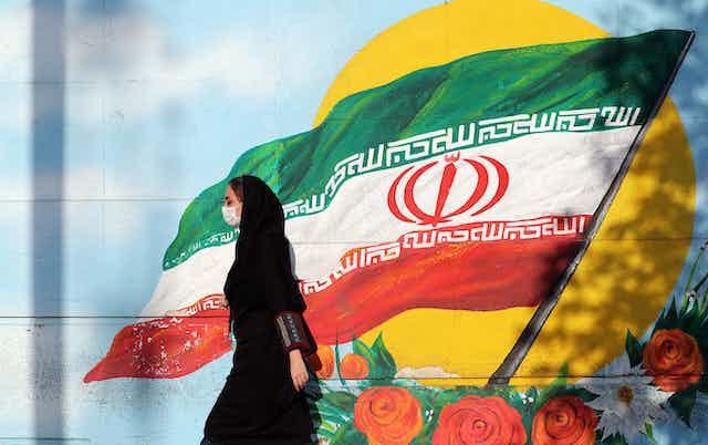 Women in Iran walks past painting of Iranian flag