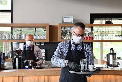 Two restaurant staff wearing masks