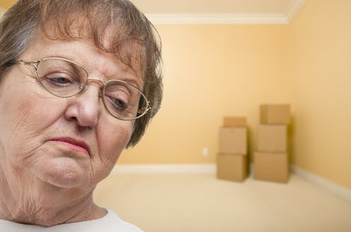 Older woman looks sad as she prepares to move house with packing boxes in an empty room
