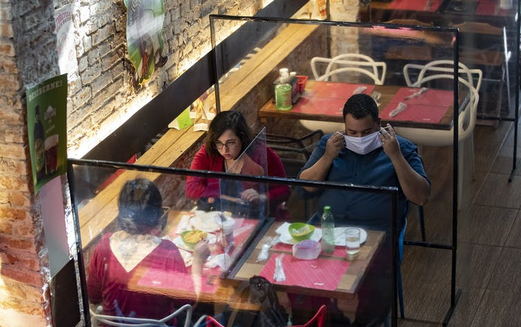 People sitting at a table at a restaurant with glass walls around them