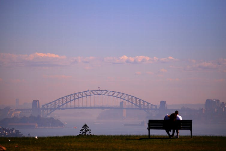 A couple on a bench look at the Sydney Harbour Bridge, shrouded in smoke.