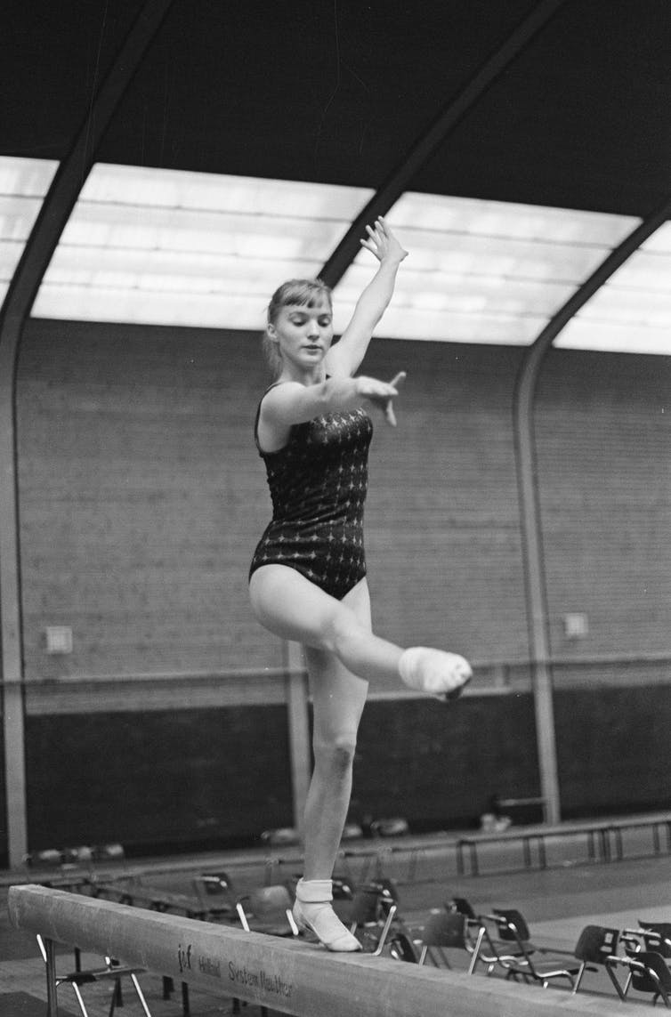 A teenage girl wears a leotard and stands on a beam.