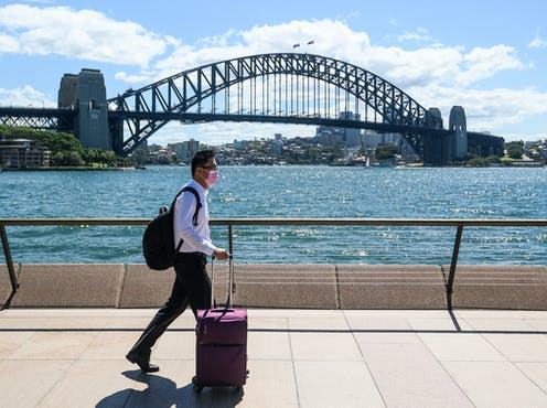 A man wearing a surgical mask walks in front of the Sydney Harbour Bridge.