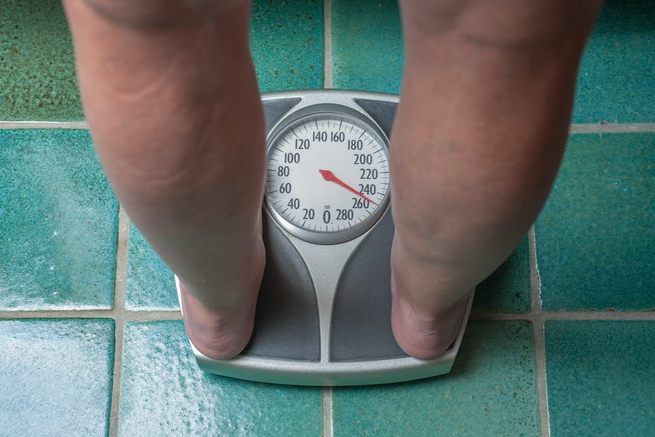 Person stands on bathroom scale.
