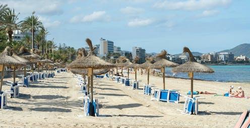 playa vacía con sombrillas y sillas apiladas.