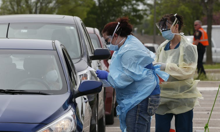 Two health care works standing outside preparing to perform a swab test at a drive-through testing station.