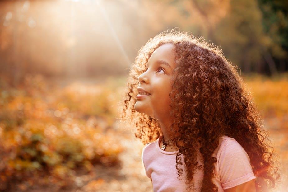 Seorang gadis muda memandang ke matahari.