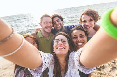 un grupo de chicas y chicos se hacen una foto en la playa
