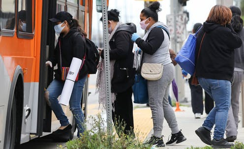 People wearing face masks board a bus in South Los Angeles in April 2020.