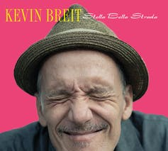 Kevin Breit wears a fedora and squints his eyes closed, while smiling against a fuschia background.