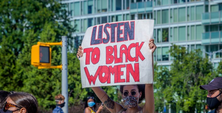 A participant holds a 'Listen to Black Women' sign at a protest in Fort Greene Park in Brooklyn, NY.