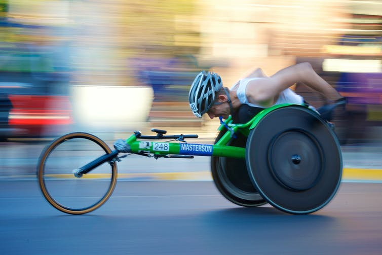 A wheelchair athlete wearing a helmet, his head bowed, racing in his bright green racing wheelchair.