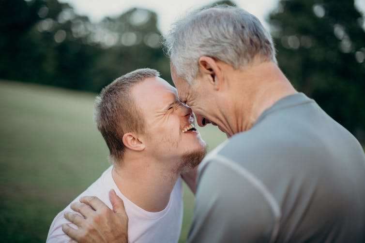 A man with disabilities smiles and rubs noses with his father in a park.