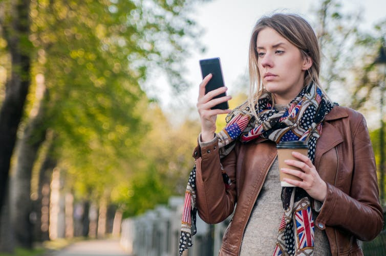 Young woman looking concerned, while looking at her phone.