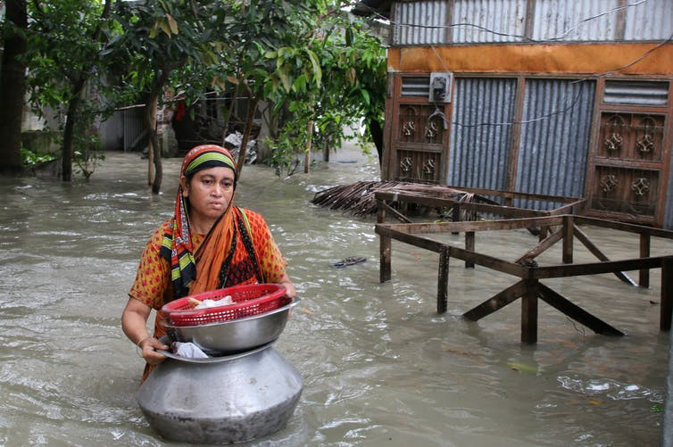 A woman struggles through floodwaters in Bangladesh
