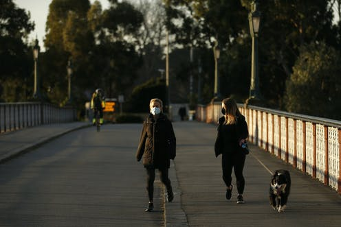 Two women wearing masks walk along a bridge. One has a dog.