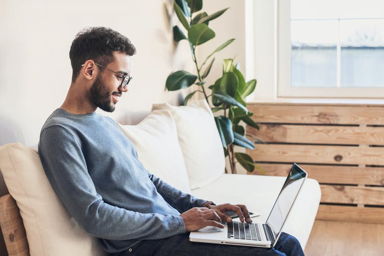 A person enjoying working on their laptop at home