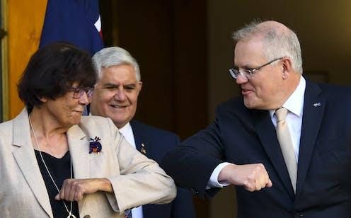 Indigenous leader Pat Turner elbow bumping Prime Minister Scott Morrison, as Minister for Indigenous Affairs Ken Wyatt looks on, smiling