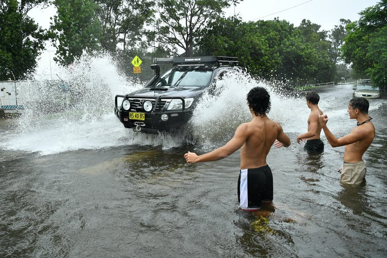 Three boys wading in floodwater direct a car through a suburban street