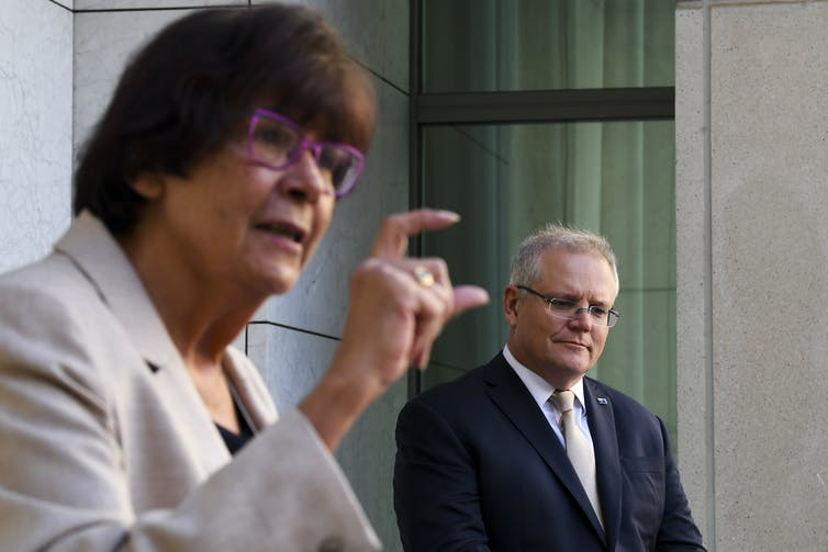 Pat Turner measuring an amount with her hand, with Scott Morrison in the background.