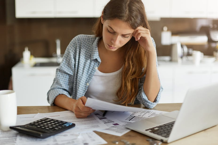 Worried woman looking at bills.