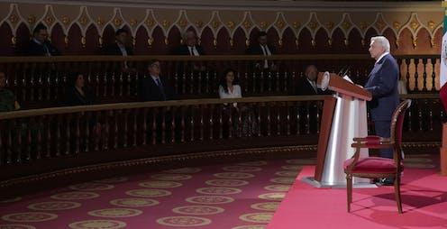 El presidente de México, Andrés Manuel López Obrador. lee un discurso ante una audiencia que escucha entre sombras.
