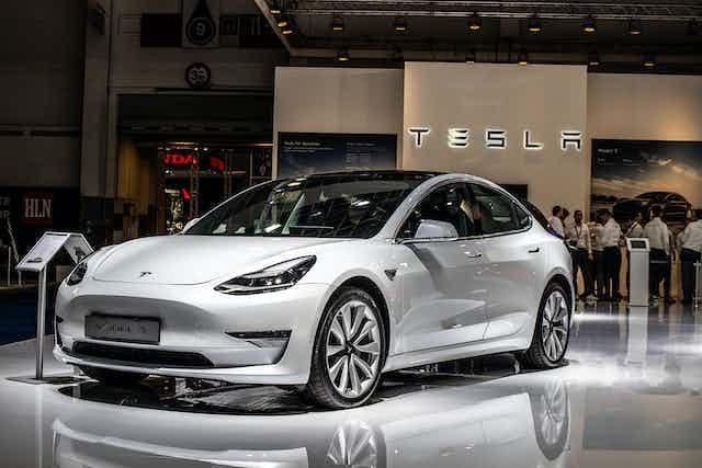White Tesla Model 3 car on motor show stand