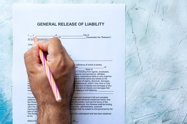 A man's hand grasps a pink pencil and prepares to sign a liability waiver.