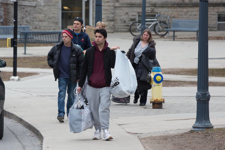 Students carrying bags and suitcases walk in a group on a grey sidewalk.