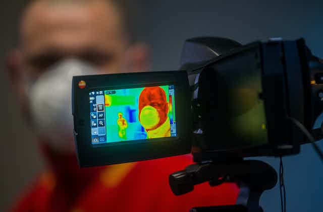 A man has his temperature taken with an infrared thermal camera.