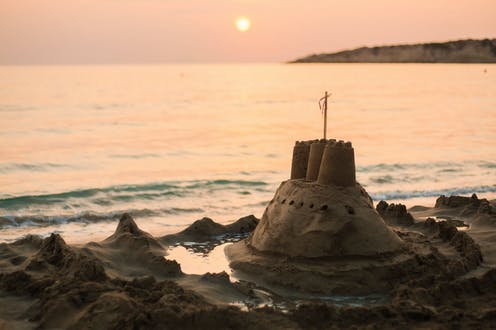 A sand castle is overtaken by the tide at dusk.