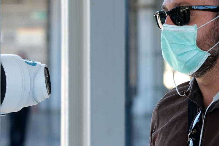 A man wearing a mask has his temperature taken by a thermal camera in Athens.
