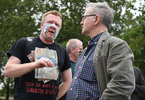 A man wears a broken facemask as a protest.