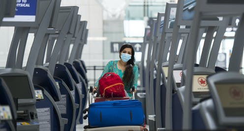 A woman with long dark hair wearing a mask pushes her luggage cart between rows of empty check-in kiosks at Toronto's Pearson airport.
